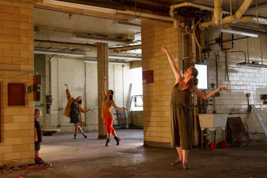 "Wild Space will perform its site-specific October show, ""Acts of Discovery,"" in a building being renovated at 1633 E. North Ave. Dancers Danielle Lohuis (yellow jacket), Elizabeth Roskopf (orange pants) and Nicole Spence (green) explore the space, while Danielle's son Euan watches."