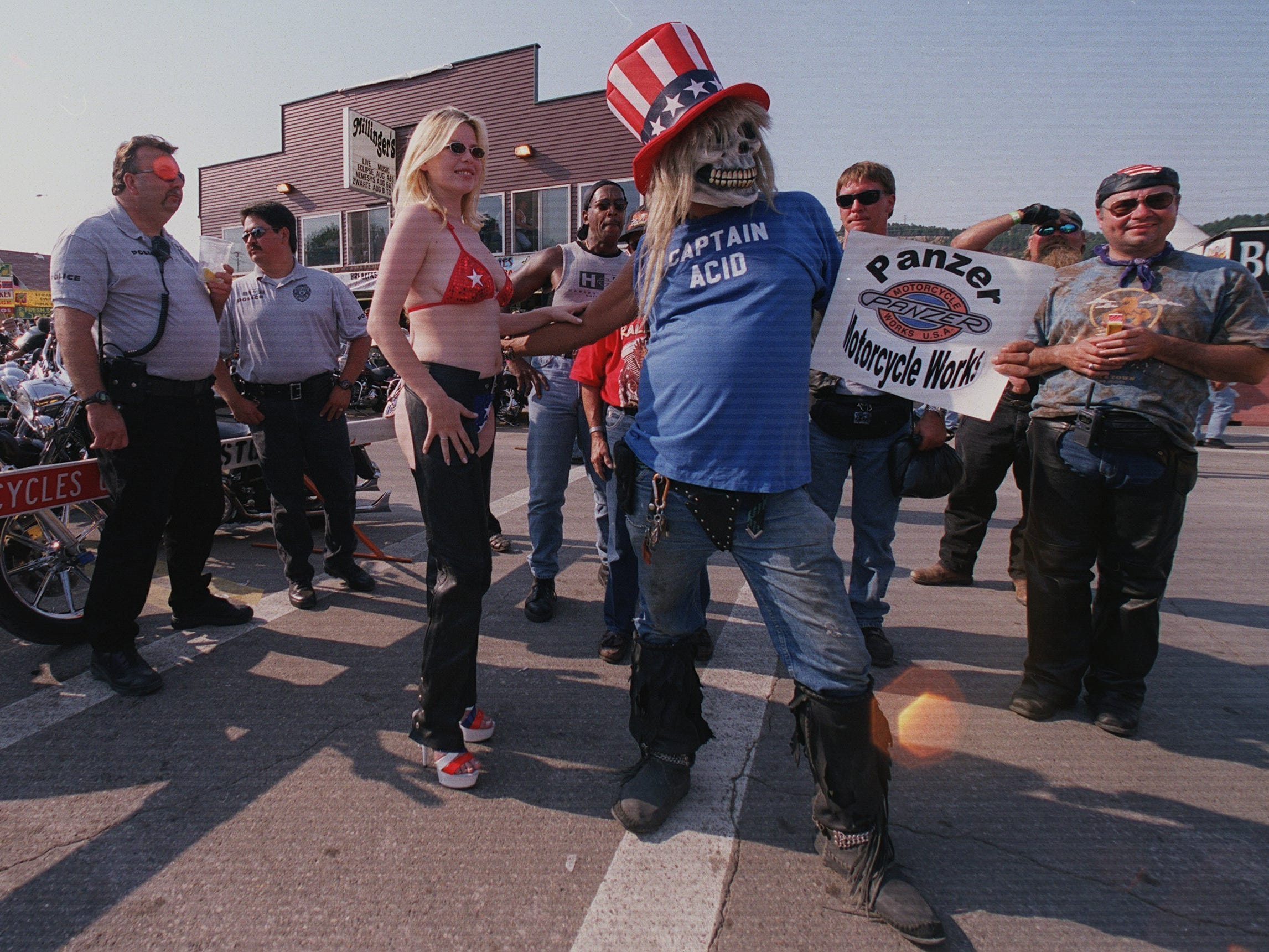 2001: While a pair of police officers keep an eye on downtown activities, a woman clad in leather chaps and a bikini is escorted by a man promoting Panzer Motorcycle Works during bike week in Sturgis, S.D. Panzer is small Colorado-based motorcycle maker. Most manufacturers find it essential to have a presence at the event.