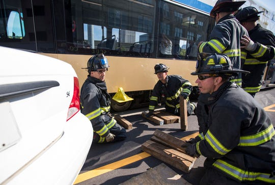 Milwaukee firefighters prepare to lift the front of the streetcar using timbers to elevate the height to add the air bags. The air bags will then inflate to raise the streetcar.