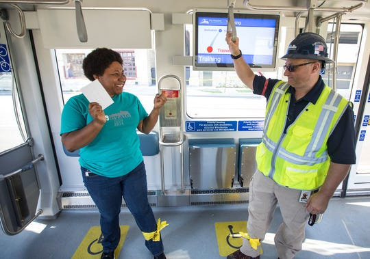 Luereatha Miller, who works for the City of Milwaukee, is given a card stating she is a person with no reports of pain or injury. Next to her is safety supervisor Brian Hinkle, who is asking each passenger if they are OK.