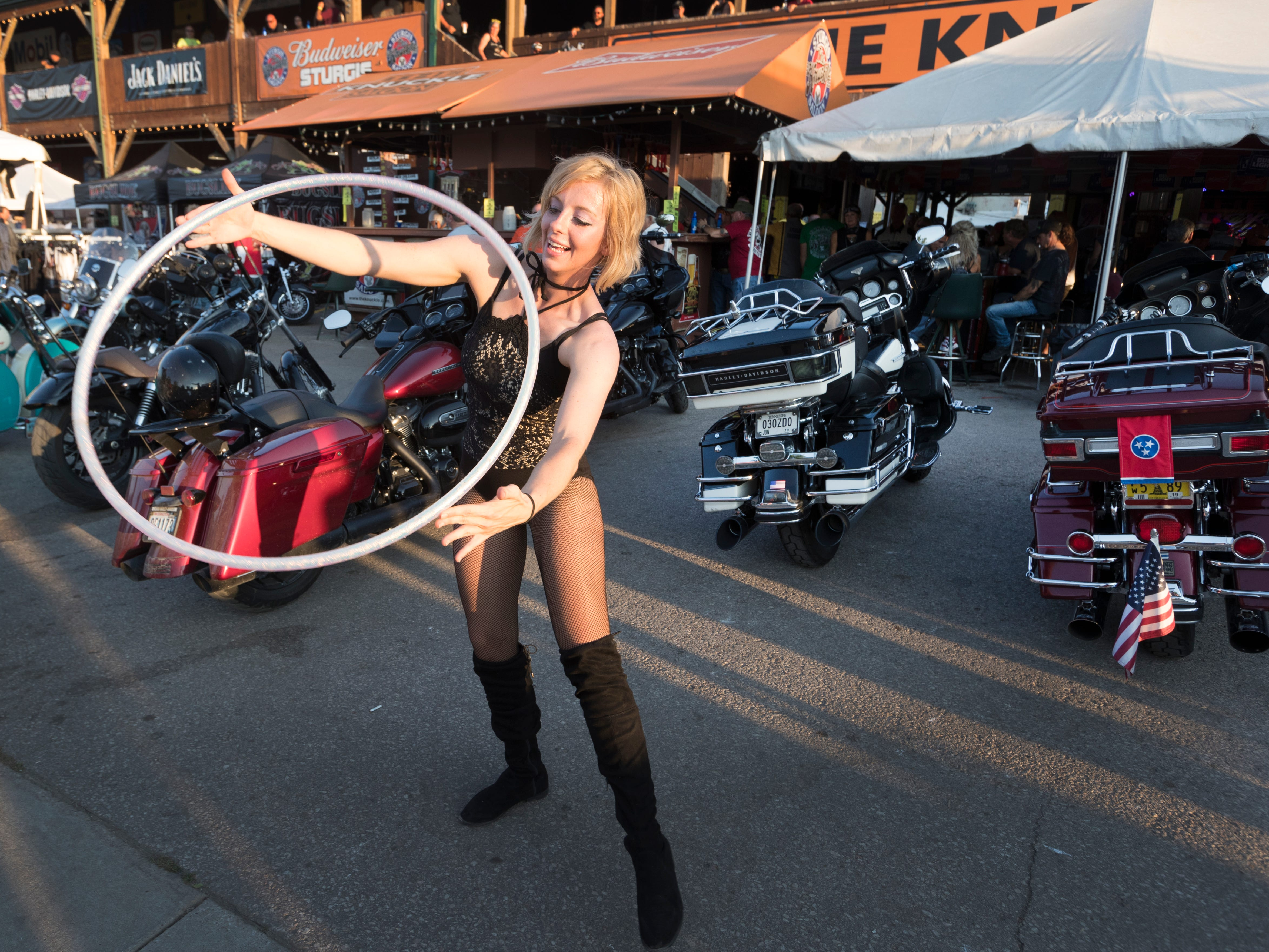 2018: A woman dances with a hoop to entice customers into a bar during the  Sturgis Motorcycle Rally.