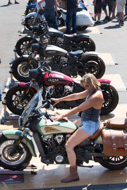 c6d5fe4f3 A woman browses Indian Motorcycle's model offerings a few hundred yards  away from Harley-Davidson's