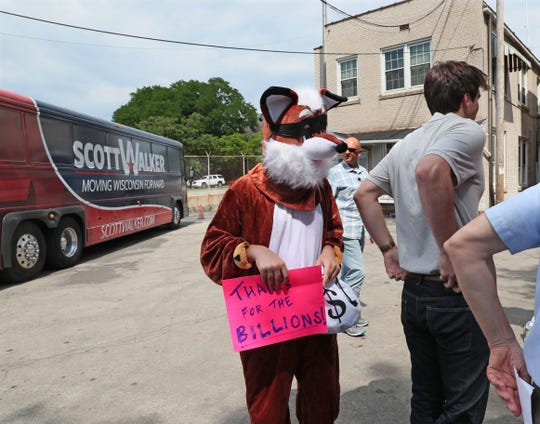 A protester dressed in a fox costume sneaked into the Walker rally but was escorted off the property at Maynard Steel Casting Co.