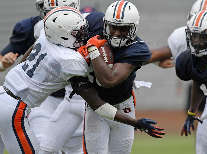 Auburn running back Asa Martin is tackled by safety Smoke Monday during a scrimmage on Thursday, Aug. 9, 2018 in Auburn, Ala.