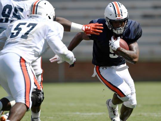 Kam Martin runs during scrimmage Thursday before being tackled by Deshaun Davis. Auburn football scrimmage on Thursday, Aug. 9, 2018 in Auburn, Ala.