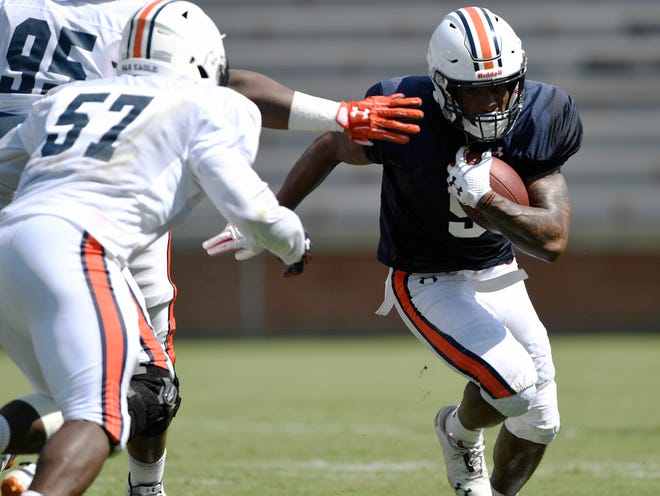 Kam Martin runs during scrimmage Thursday before being tackled by Deshaun Davis. Auburn football scrimmage on Thursday, Aug. 9, 2018 in Auburn, Ala.