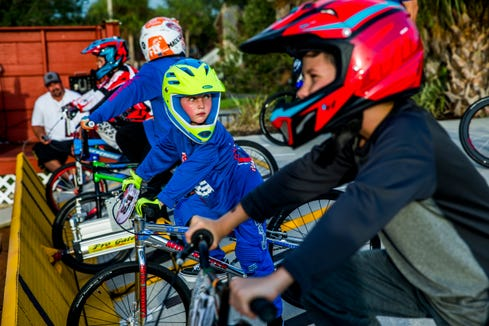 Riders line up along the starting gate for one of the Wednesday night races at the Naples BMX track in Golden Gate City on Wednesday, Aug. 8, 2018.
