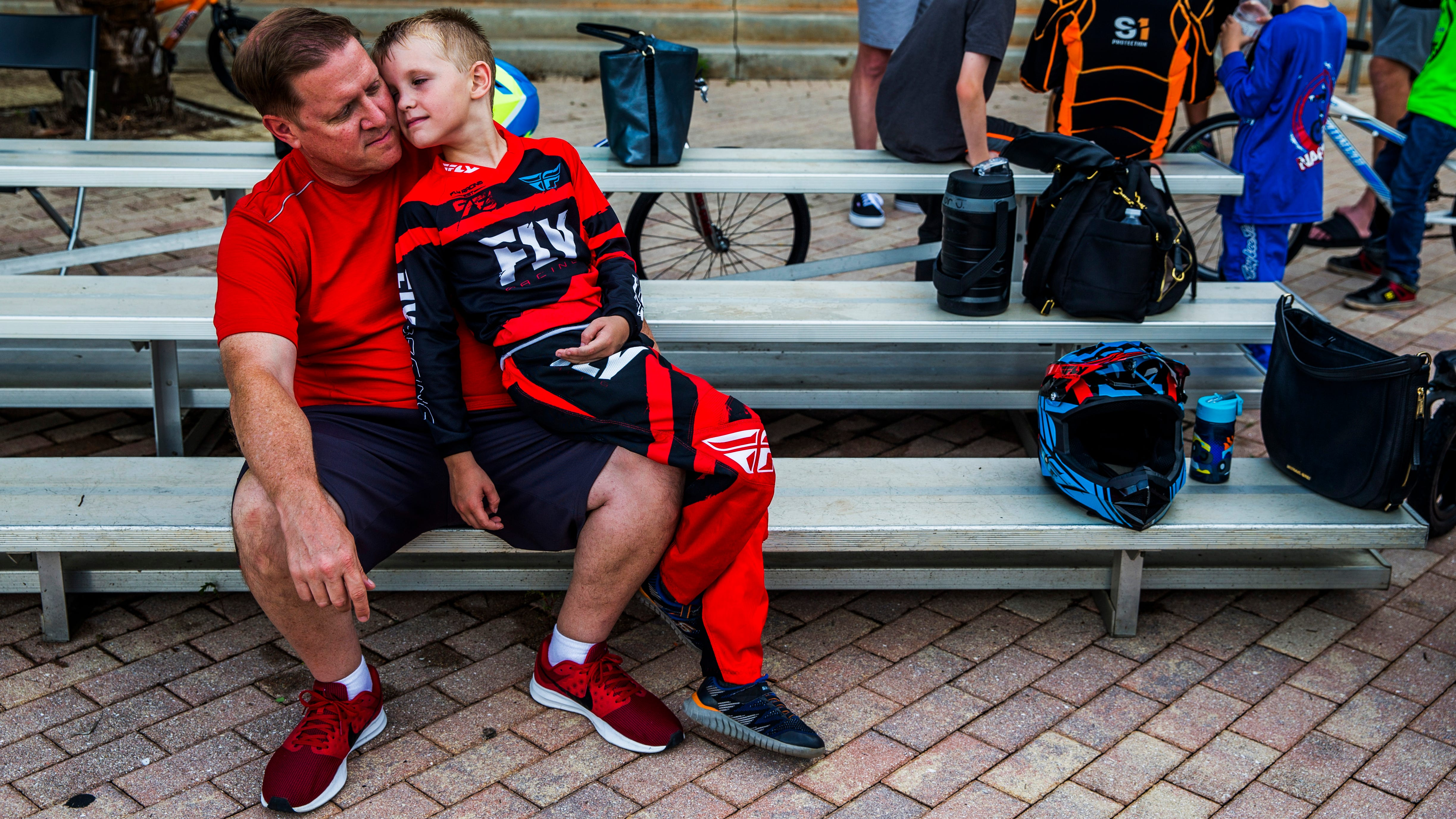 Scott Jackson of Naples snuggles with his son Trevor, 6, before the Wednesday night races begin at the Naples BMX track in Golden Gate City on Wednesday, Aug. 8, 2018.