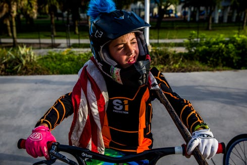 With an American flag around his shoulders, Sebastian Tranchand, 9, of Naples waits to begin the pre-race ceremonial lap at the Naples BMX track in Golden Gate City on Wednesday, Aug. 8, 2018.