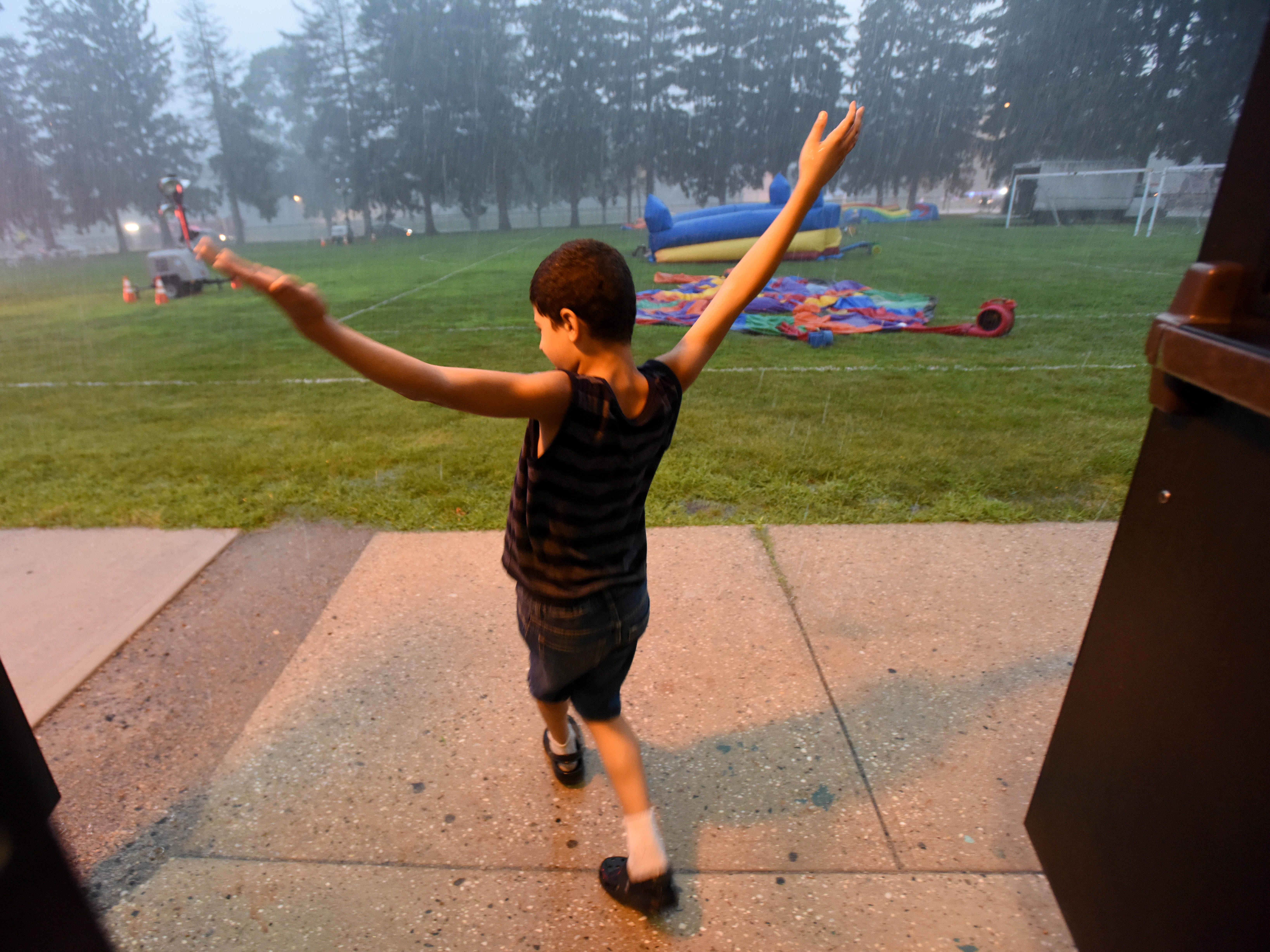 Nine-year-old Liam Lynch steps outside New Milford High School' auditorium as National Night Out  is rain out.