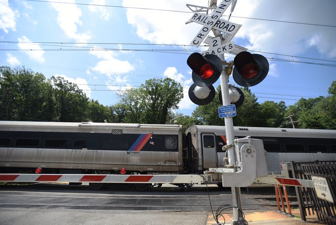 A NJ Transit commuter train at a grade crossing.