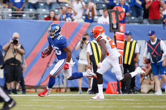 New York Giants running back Saquon Barkley (26) runs past Cleveland Browns' Jabrill Peppers (22) during the first half of a preseason NFL football game Thursday, Aug. 9, 2018, in East Rutherford, N.J. (AP Photo/Adam Hunger)