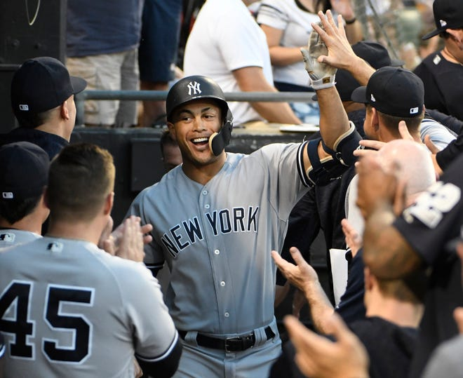 New York Yankees' Giancarlo Stanton, center, is greeted in the dugout after hitting a grand slam against the Chicago White Sox during the second inning of a baseball game Wednesday, Aug. 8. (