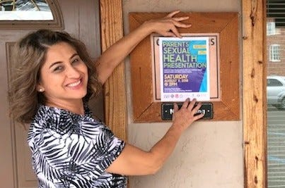 Mirna Chairez of parents as Teachers, puts up a flyers for Saturday's Parnets' Sexual Health Presentation at the historic Train Depot.