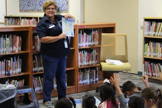 Las Cruces Utilities Water Conservation Program Coordinator Rhonda Diaz explains the water cycle to children at University Hills Elementary School's K3+ program.
