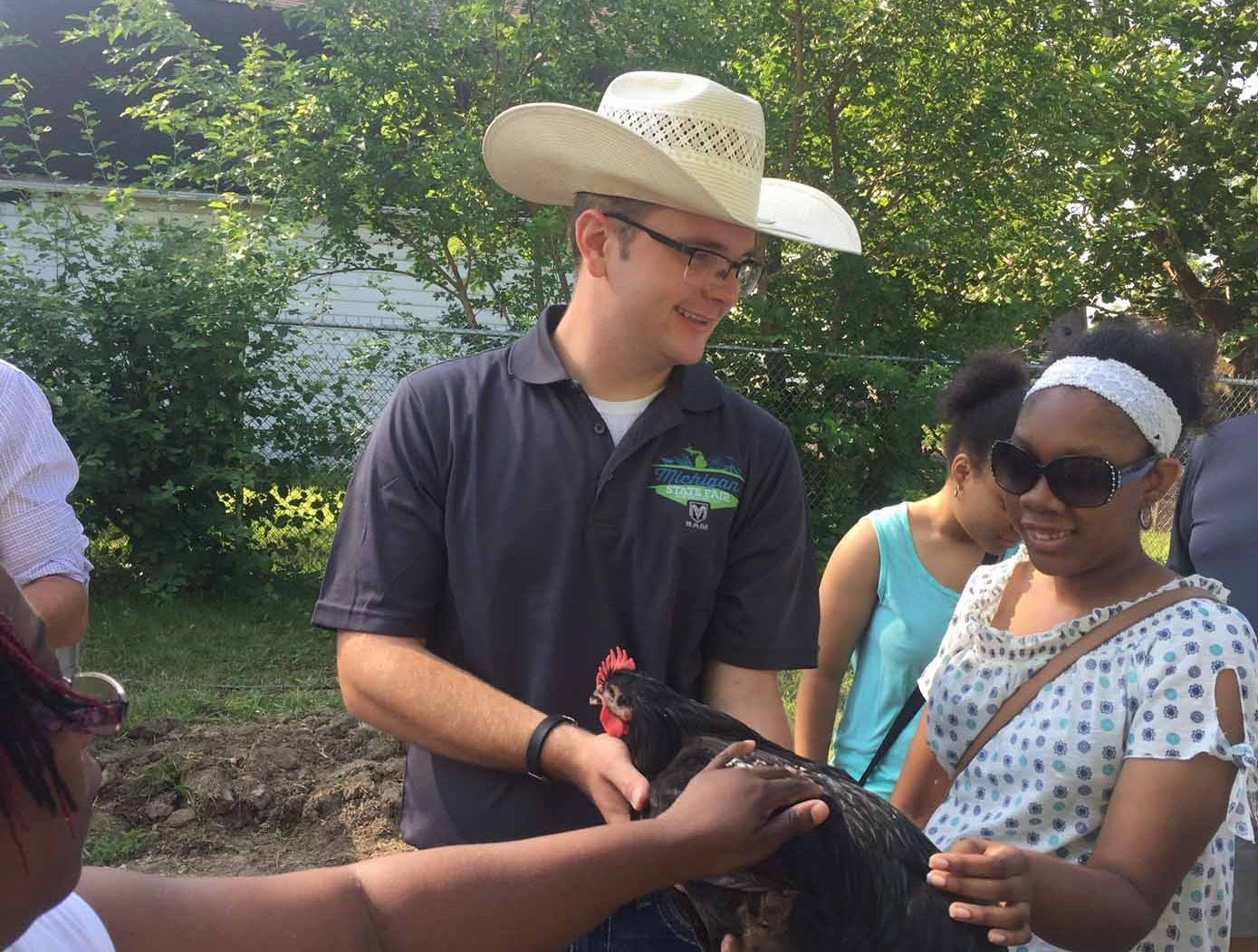 Michigan State Fair youth council's Tom Purves works with Detroit youth to help raise chickens at Oakland AvenueUrban Farm in Detroit.