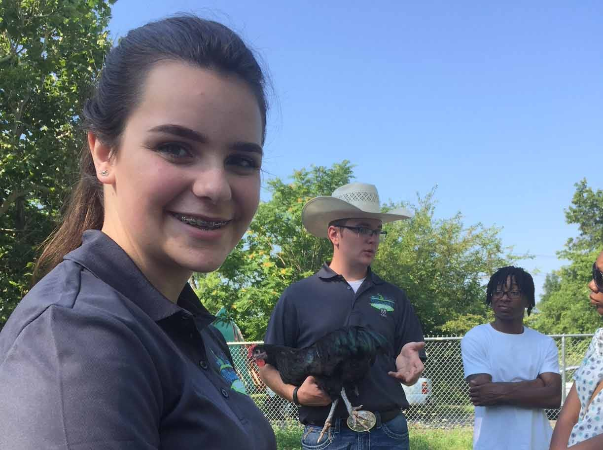 Michigan State Fair youth council's Allie Purves works with Detroit youth to help raise chickens at Oakland Avenue Urban Farm in Detroit.