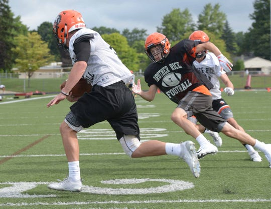 On Aug. 8 Brother Rice's Colin Gardner turns the corner on defensive player Kyle Sparks during the the third day of practice for football teams in Michigan.