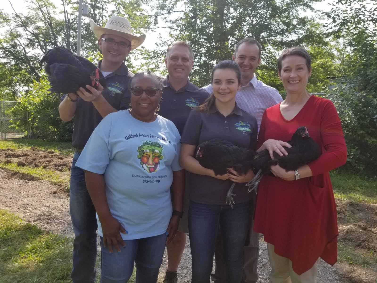 Michigan State Fair youth council work with Detroit youth to help raise chickens at Oakland Avenue Urban Farm in Detroit.