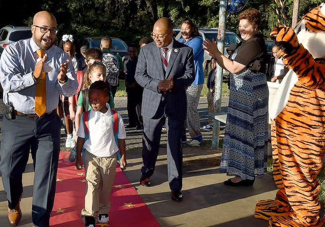 Grolee Elementary Principal Brandon Singleton, left, and St. Landry Parish School Board Superintendent Patrick Jenkins leads students down the red carpet as they begin Thursday. their first day of the new school year. See more photos of back to school at dailyworld.com and on the Daily World Facebook site.
