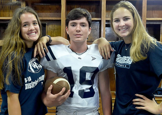 Westminster Christian Academy trainers Laura Wiltz (left) and Lessley Fontenot pose with quarterback Janssen Lacour during the football team's annual Picture Day on Wednesday.
