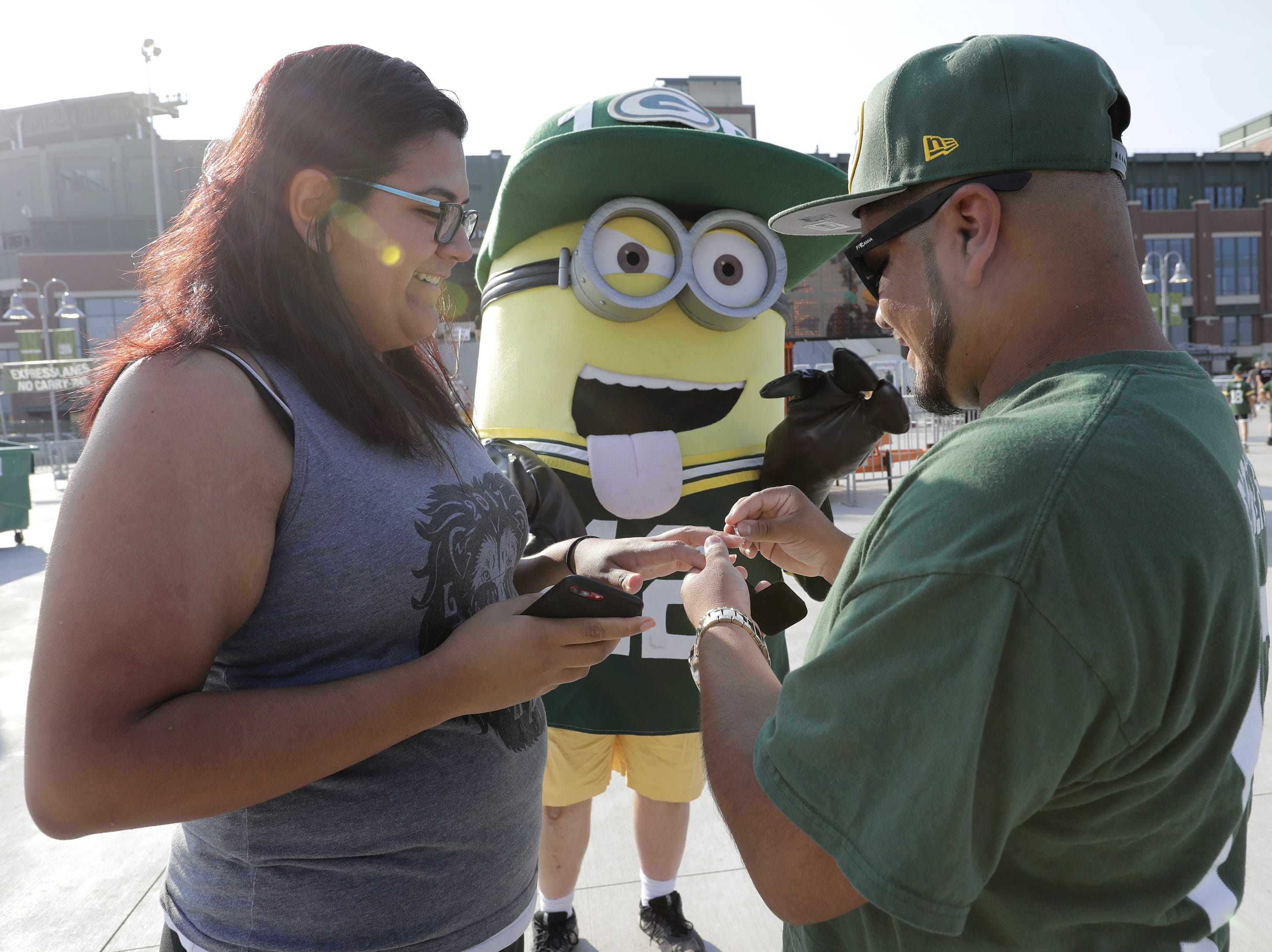 Alex Perez of Chicago proposes to Monica Rayes of Chicago prior to the Green Bay Packers football game Thursday, August 9, 2018, at Lambeau Field in Green Bay, Wis.