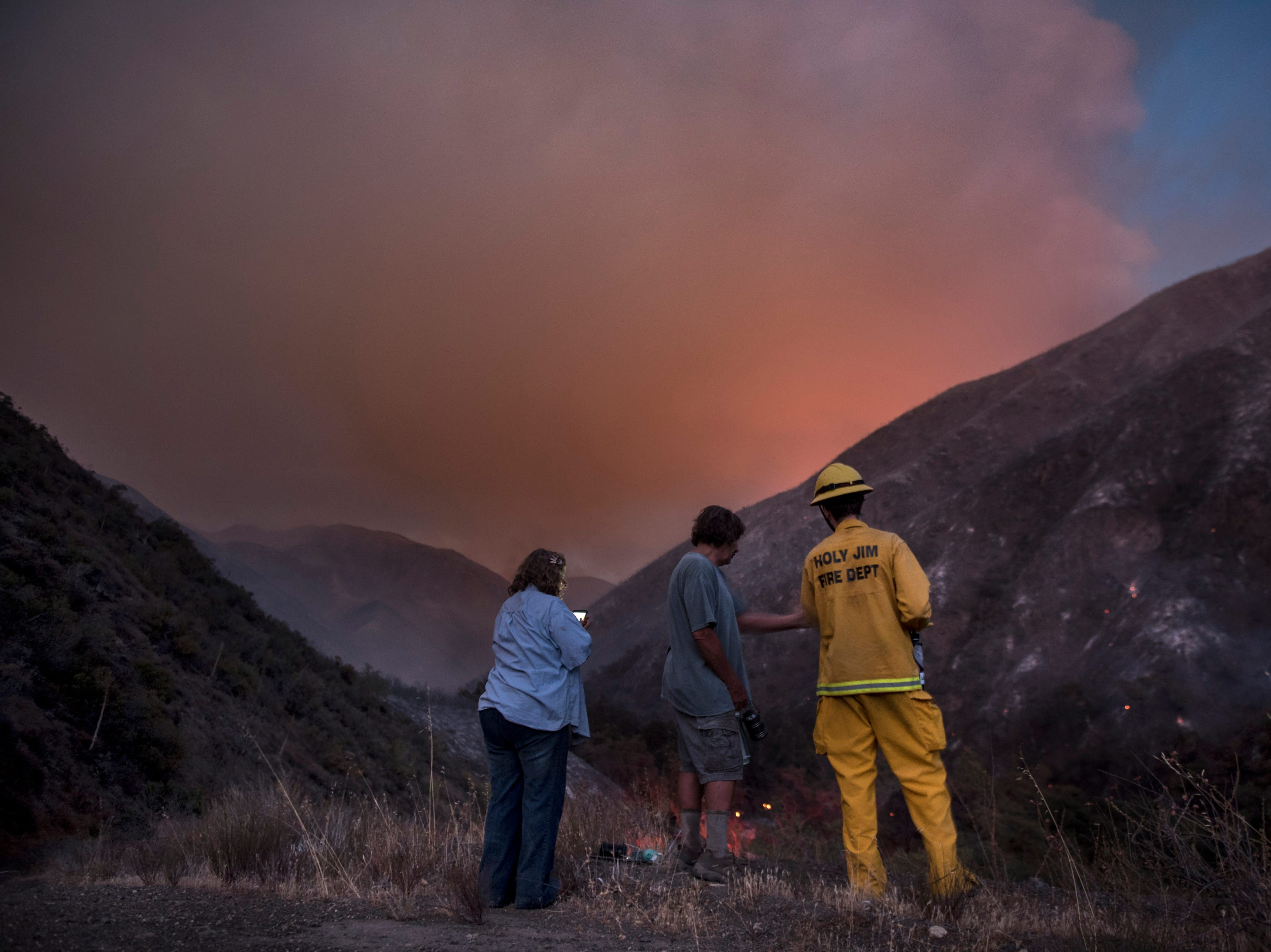 Holy Jim Canyon residents Beep and John Colclough watch firefighting efforts of the Holy Fire in Trabuco Canyon, Calif., with volunteer firefighter Luke Senger on Monday, Aug 6, 2018. (Mindy Schauer/The Orange County Register via AP)