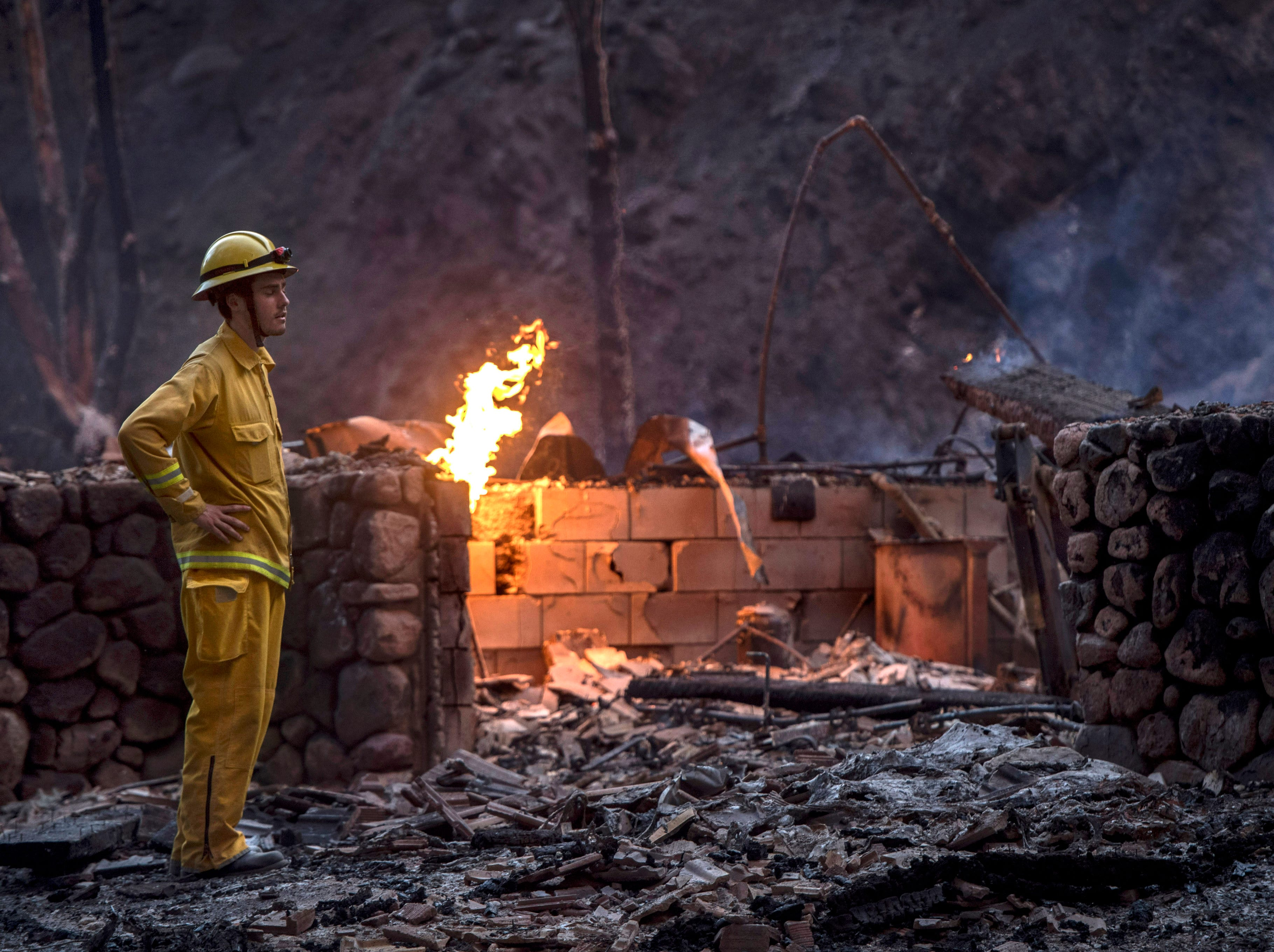 Holy Jim volunteer firefighter Luke Senger stands next to a home destroyed the Holy Fire in Trabuco Canyon, Calif., on Monday, Aug 6, 2018. (Mindy Schauer/The Orange County Register via AP)