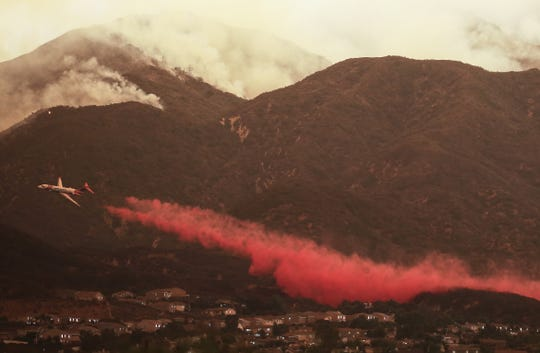 LAKE ELSINORE, CA - AUGUST 08:  A firefighting airplane drops fire retardant ahead of the Holy Fire as it burns in Cleveland National Forest on August 8, 2018 in Corona, California. The fire has burned at least 6,200 acres and destroyed twelve structures.  (Photo by Mario Tama/Getty Images)