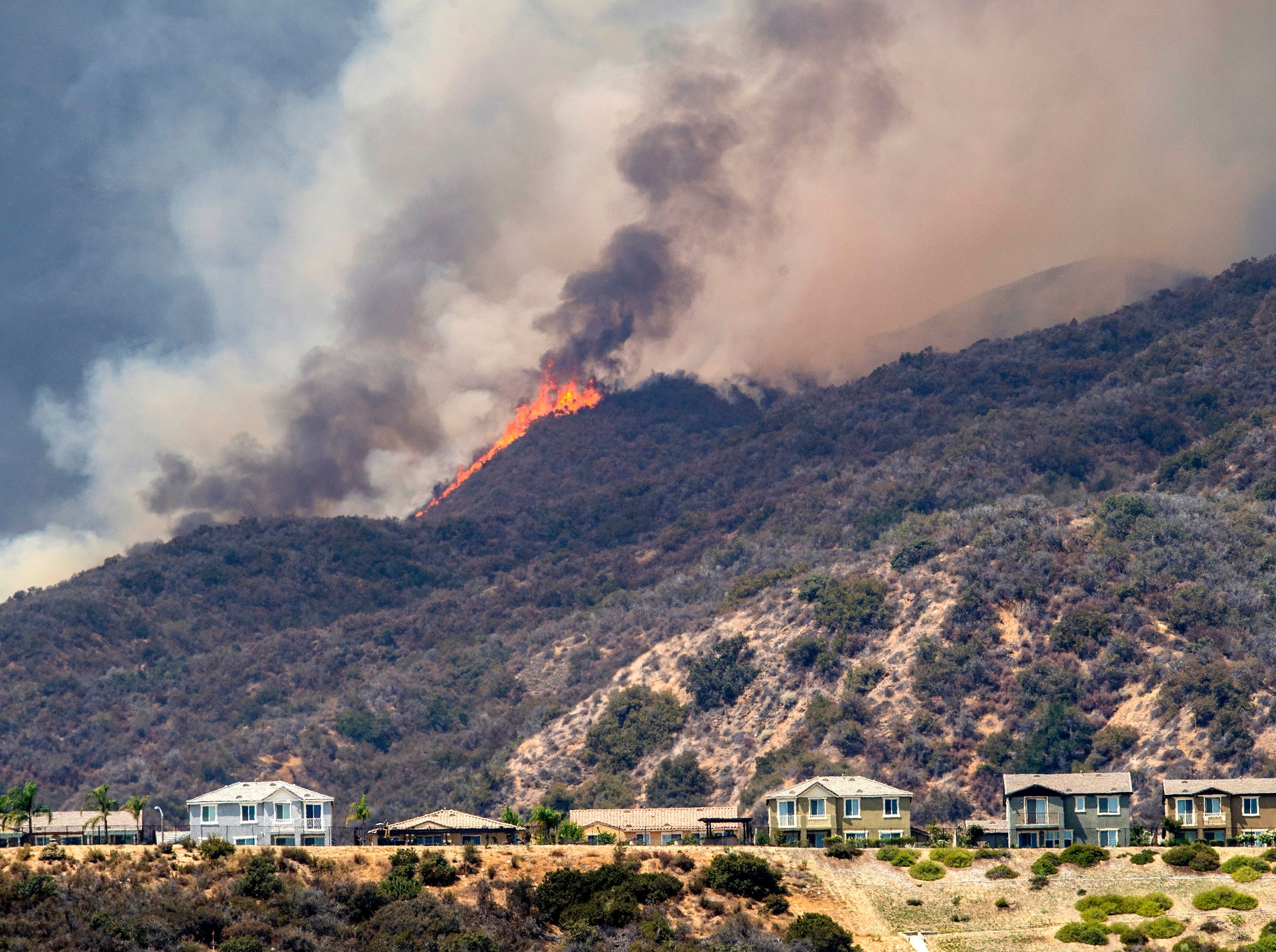 """The """"Holy Fire"""" burns near homes in Lake Elsinore, Calif., on Wednesday, Aug. 8, 2018. (Mark Rightmire/The Orange County Register via AP)"""