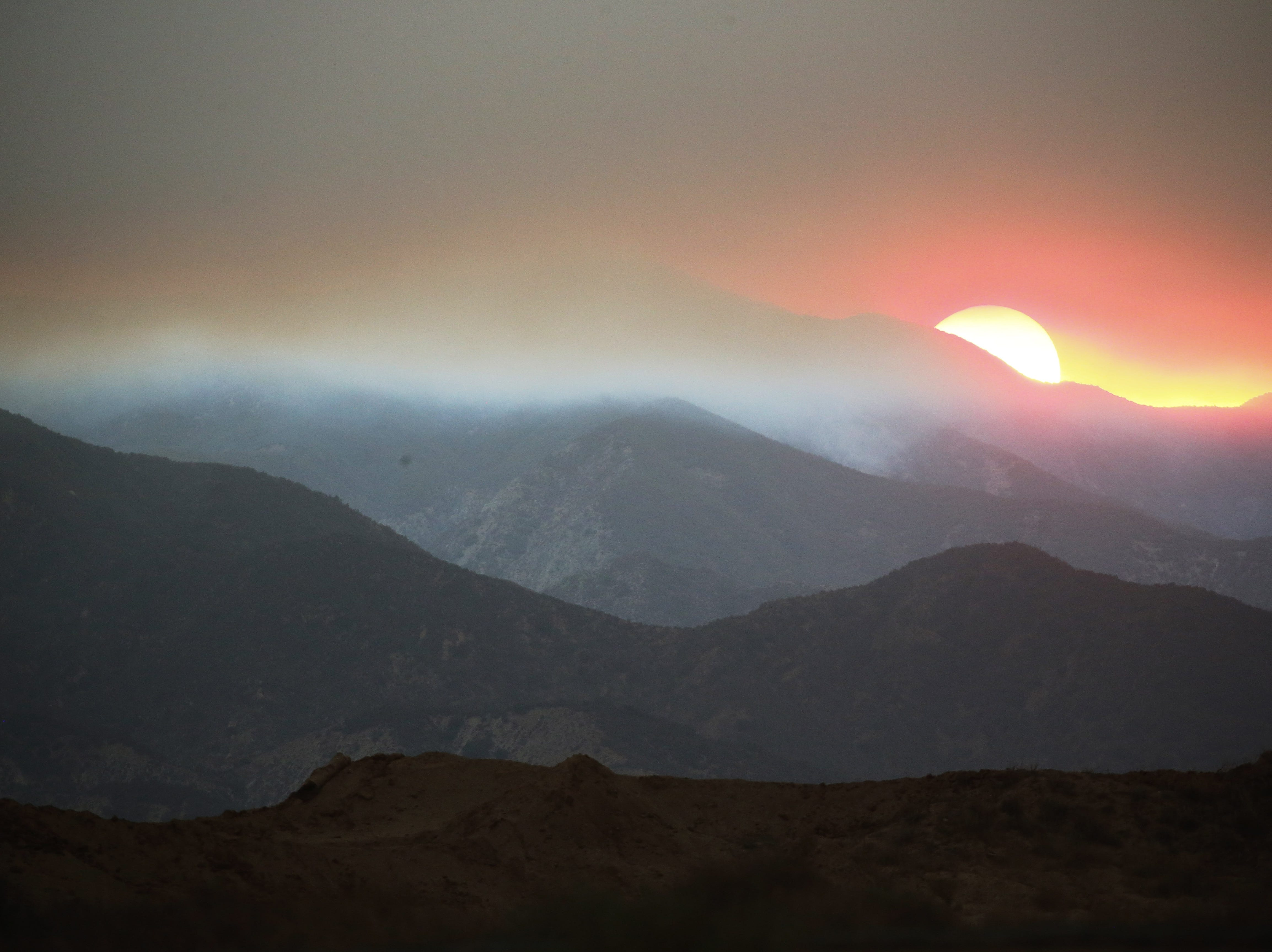 CORONA, CA - AUGUST 08:  The sun sets behind smoke from the Holy Fire in Cleveland National Forest on August 8, 2018 in Corona, California. The fire has burned at least 6,200 acres and destroyed twelve structures.  (Photo by Mario Tama/Getty Images)