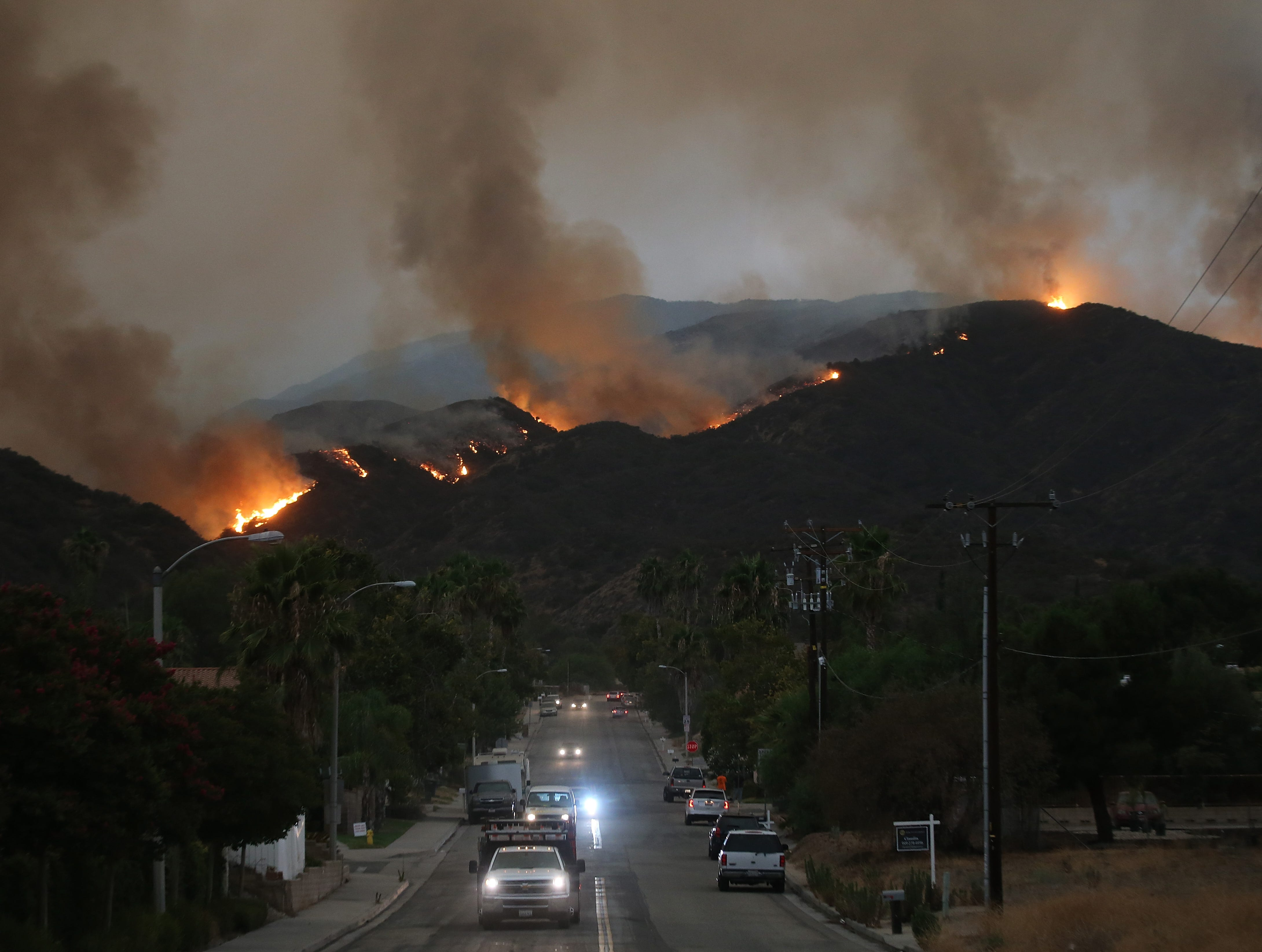 LAKE ELSINORE, CA - AUGUST 08: Cars drive down a hill in a mandatory evacuation area as the Holy Fire burns in Cleveland National Forest on August 8, 2018 in Lake Elsinore, California. The fire has burned at least 6,200 acres and destroyed twelve structures.  (Photo by Mario Tama/Getty Images)