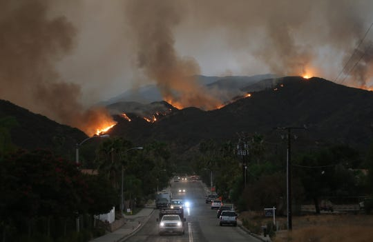 Cars drive down a hill in a mandatory evacuation area as the Holy Fire burns in Cleveland National Forest on August 8, 2018 in Lake Elsinore, Calif.