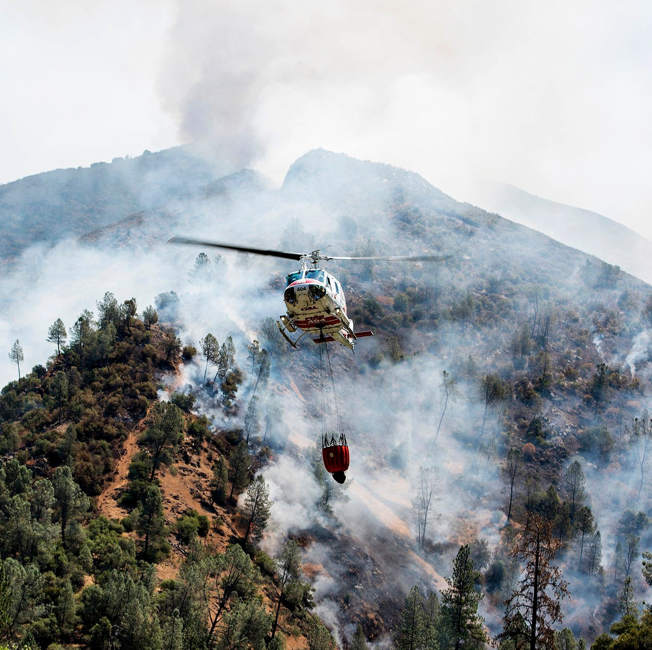 A helicopter gathers water from the Merced River to fight the Ferguson Fire along steep terrain behind the Redbud Lodge near El Portal along Highway 140 in Mariposa County, Calif., on Saturday, July 14, 2018. (Andrew Kuhn /The Merced Sun-Star via AP)