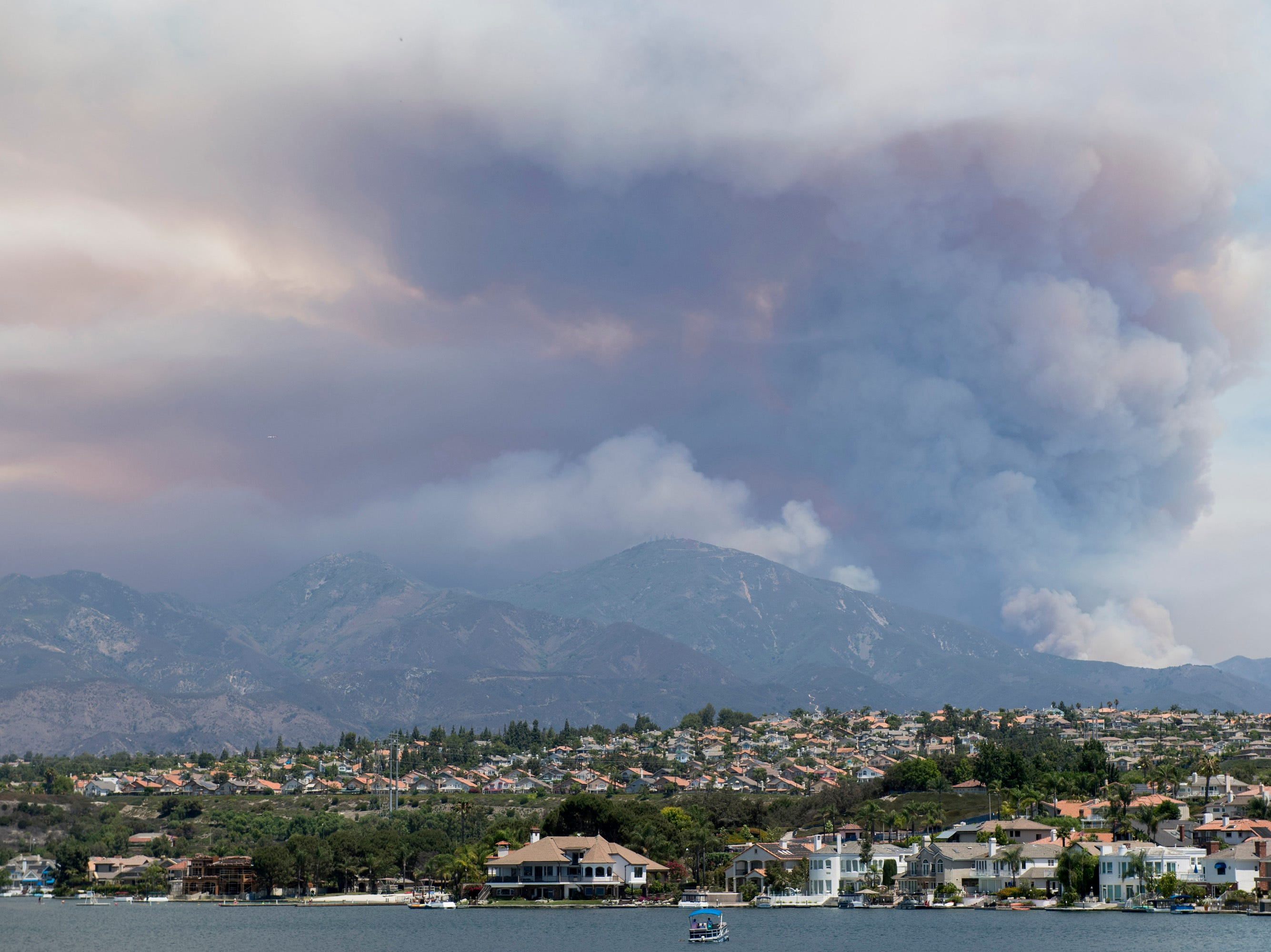 """A boat floats on Lake Mission Viejo as the """"Holy Fire"""" burns in the mountains behind Mission Viejo, Calif., on Wednesday, Aug. 8, 2018. (Kevin Sullivan/The Orange County Register via AP)"""