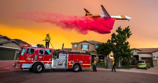A plane drops fire retardant behind homes along McVicker Canyon Park Road in Lake Elsinore, Calif., as the Holy Fire burned near homes on Wednesday, Aug. 8, 2018. (Mark Rightmire/The Orange County Register via AP)