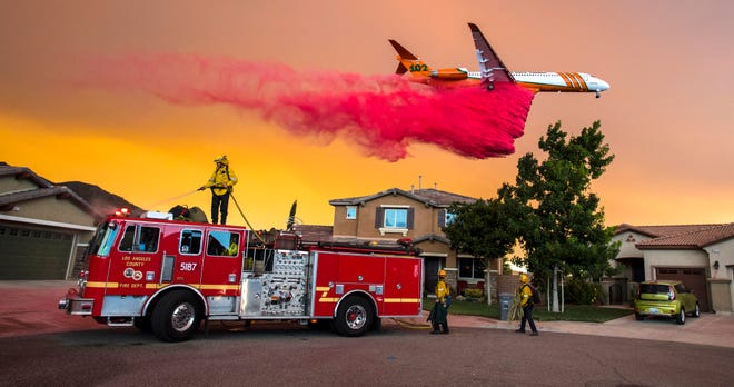 A plane drops fire retardant Aug. 8, 2018, behind homes in Lake Elsinore, Calif., as the Holy Fire burned.