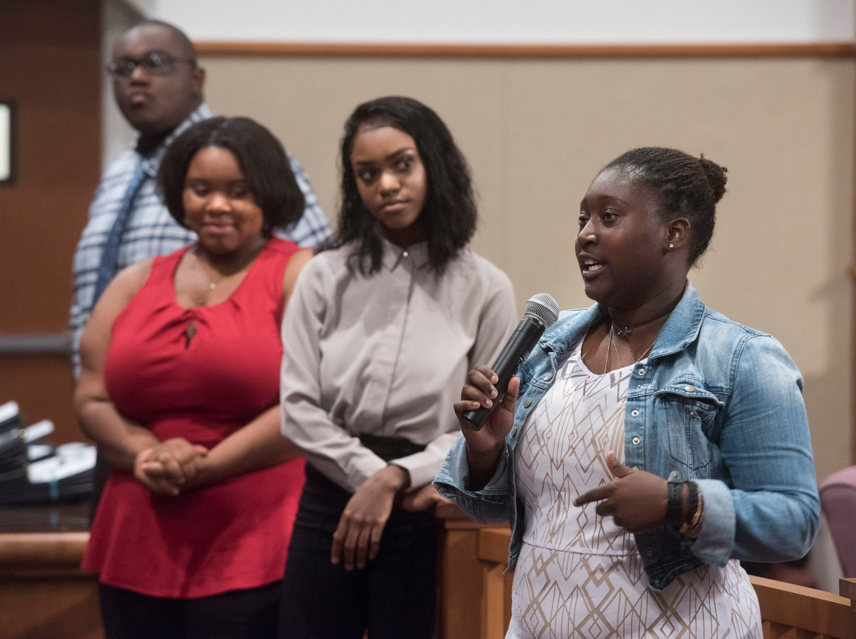 Destinee Pagett, right, praises Escambia County for its student internship program during a ceremony in the commission chambers to recognize the young workers Thursday, Aug. 9, 2018