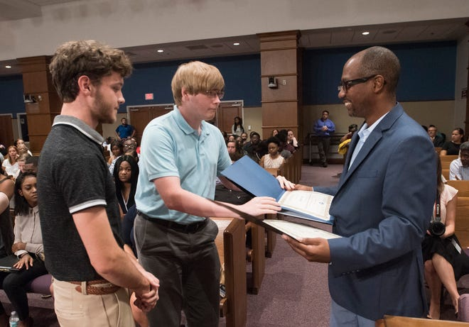 Escambia County Commissioner Lumon May presents Robert Vose and Tucker Hall with certificates Thursday for completing the county's Youth Employment Program.