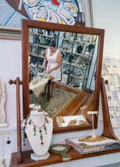 Gallery manager Adrianna Collins straightens some of the jewelry made by owner Diencha Marsh at the Ann David Gallery off Cervantes Street in East Hill, Pensacola on Wednesday, August 8, 2018.
