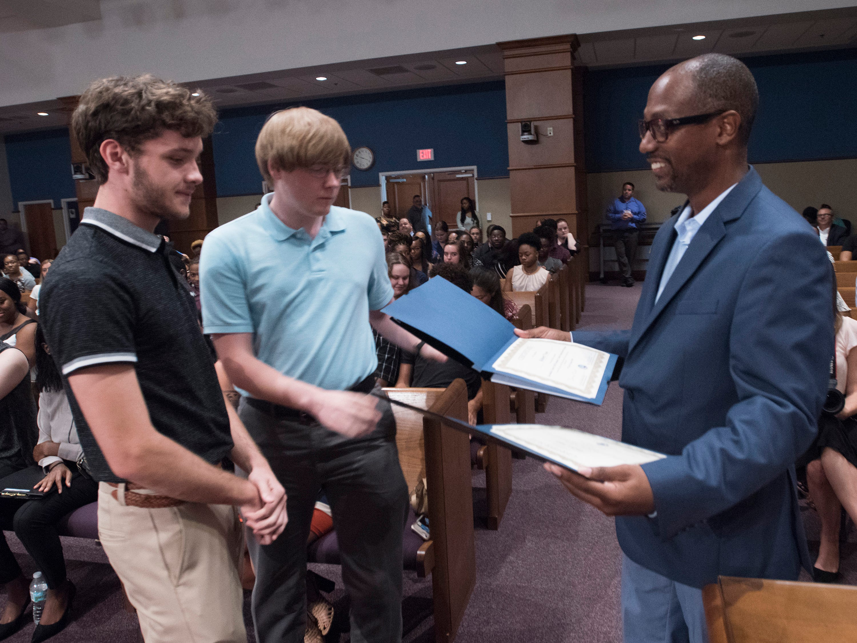 Escambia County Commissioner, Lumon May, presents, Robert Vose and Tucker Hall with certificates of completion during a ceremony in the commission chambers, Thursday, Aug. 9, 2018, to recognize the work of student interns.