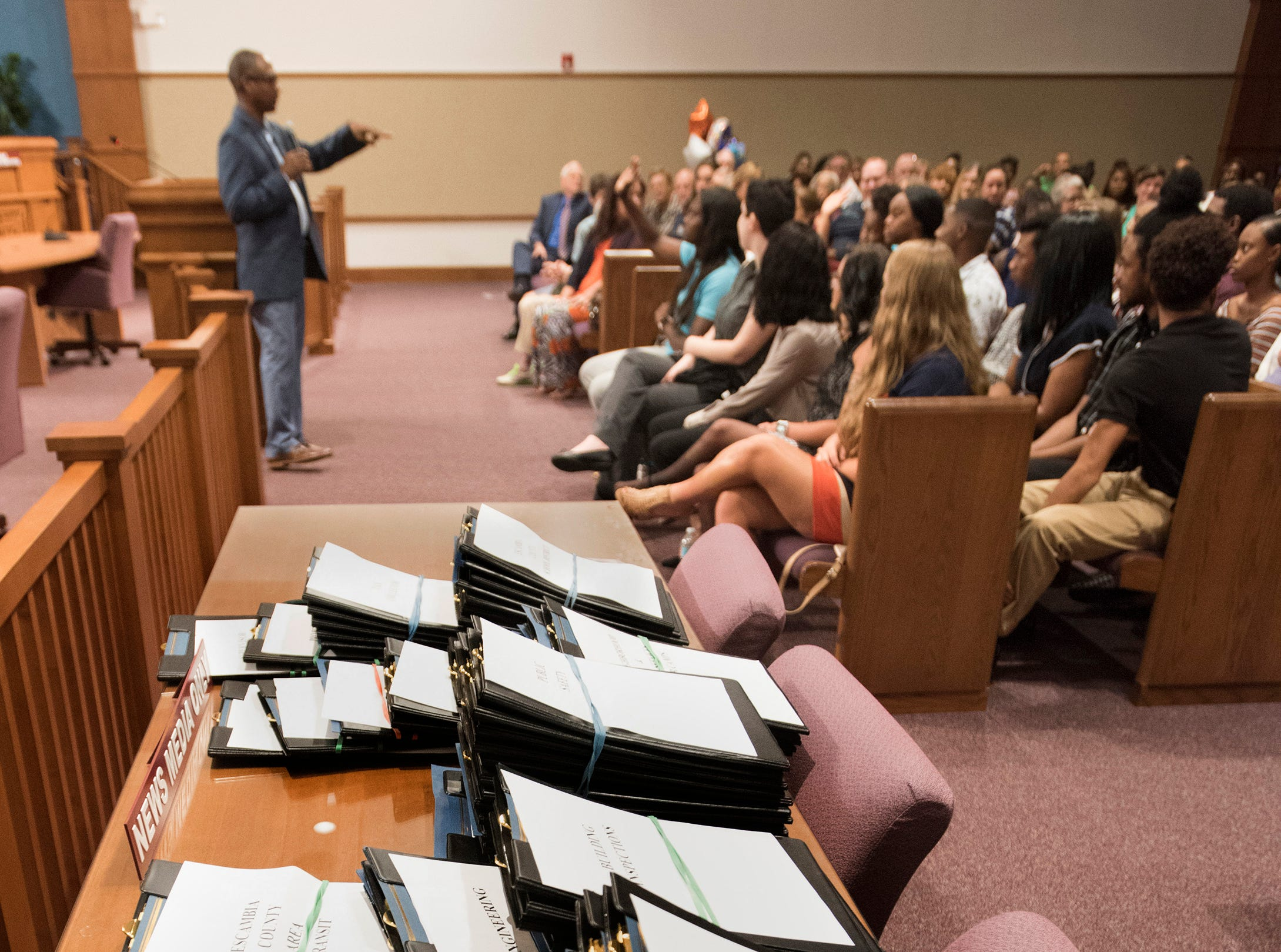Escambia County Commissioner, Lumon May, addresses a group of interns during a ceremony in the commission chambers, Thursday, Aug. 9, 2018,  to recognize the hard work of the student workers.