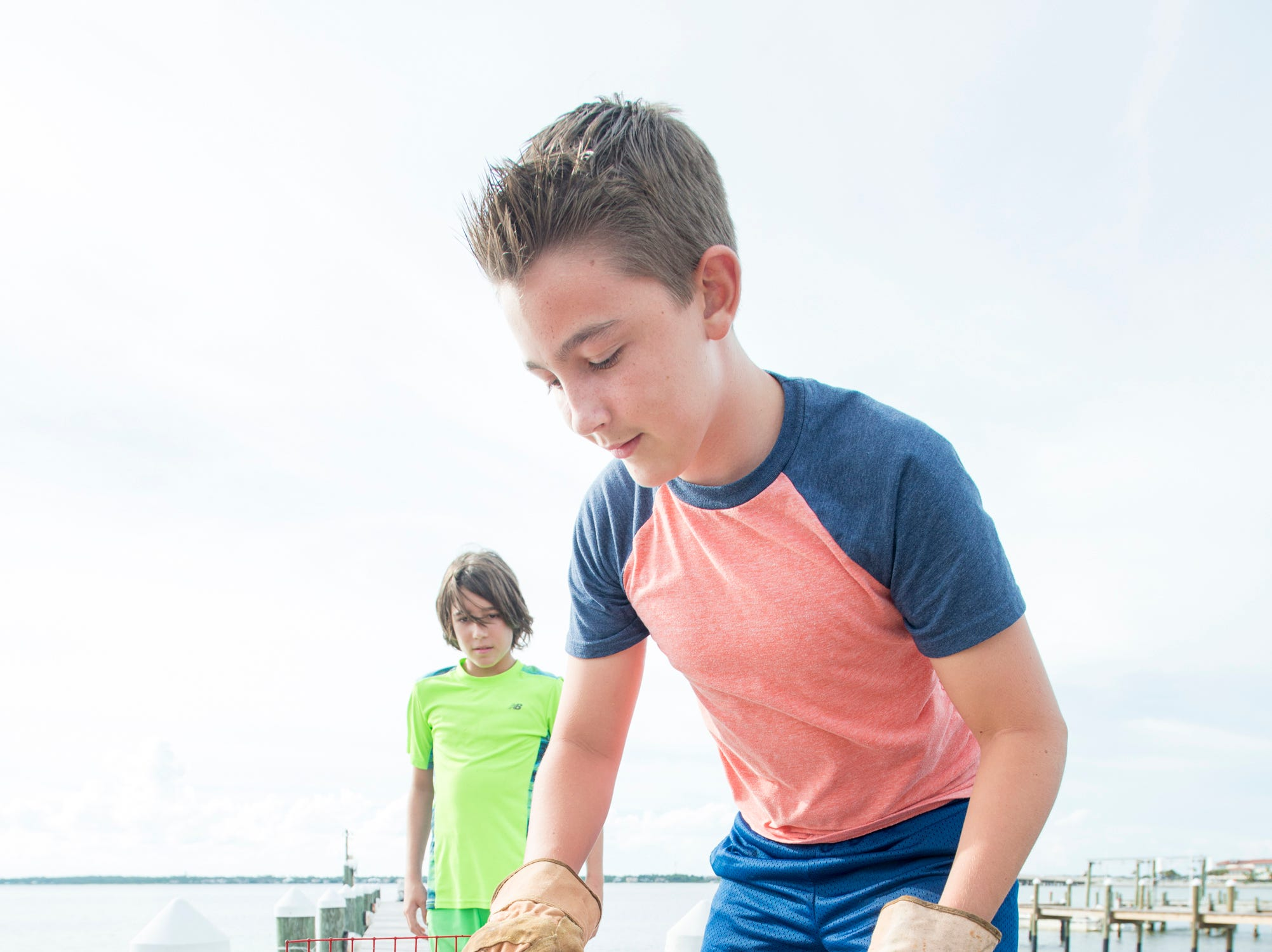 Ryan Kalb, 10, left, looks on as his brother Ben Kalb, 12, removes the three-clawed blue crab that he recently caught from the trap behind their home on Little Sabine Bay in Pensacola.   Thursday, August 9, 2018.