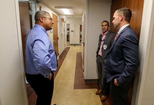 From left, physician assistant Jean Bernard Le Gall; Brett Aldridge, executive director of business development, strategic planning and partnerships at Baptist Health Care; and Bobby Potomski, director of primary care services at Baptist Health Care, chat Thursday during an open house at Baptist Medical Group's new walk-in clinic in downtown Pensacola.