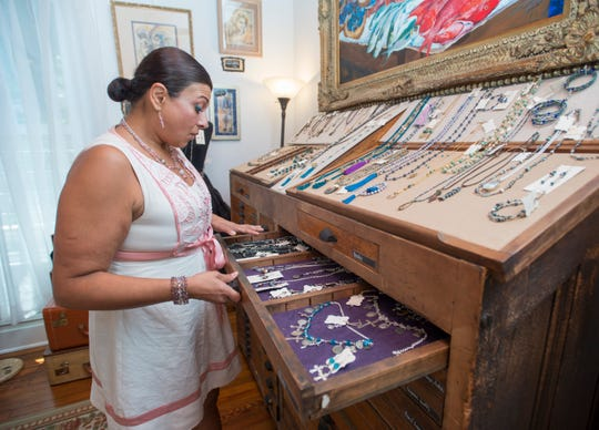 Gallery manager Adrianna Collins talks about some of the jewelry made by owner Diencha Marsh at the Ann David Gallery off Cervantes Street in East Hill, Pensacola on Wednesday, August 8, 2018
