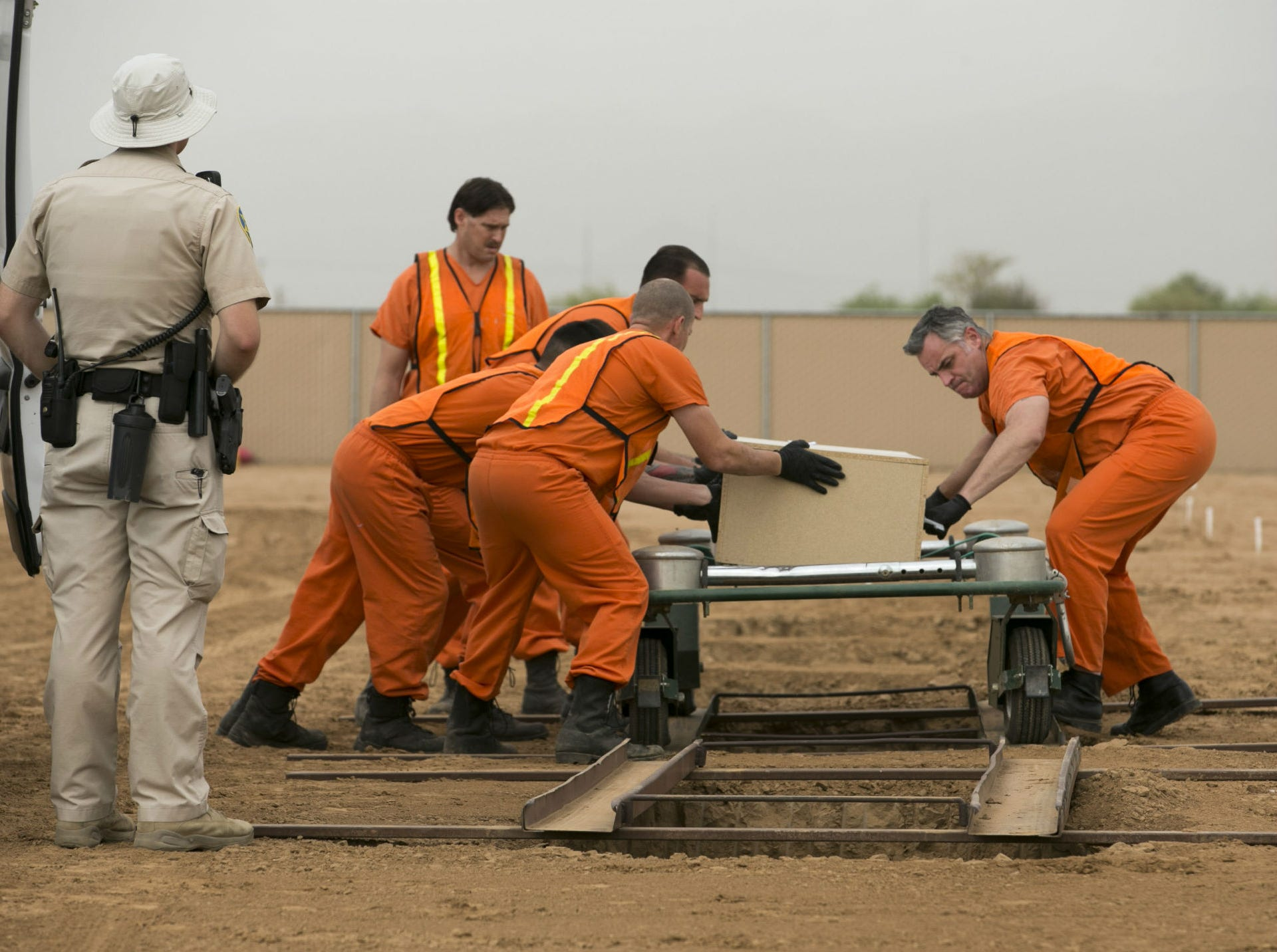 Maricopa County jail inmates assist with the burial of an indigent individual as a Maricopa County corrections officer keeps a watchful eye at the White Tanks Cemetery in Litchfield Park on Aug. 9, 2018.