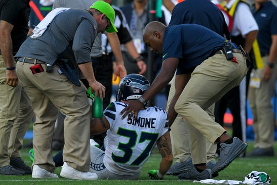 Seattle Seahawks safety Jordan Simone is helped by team officials after an injury during a 2017 NFL preseason game against the Los Angeles Chargers in Carson, Calif.