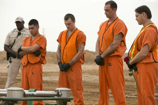 Maricopa County jail inmates bow their head in prayer as they assist with the burial of an indigent individual while a Maricopa County correction officer keeps a watchful eye at the White Tanks Cemetery in Litchfield Park on Aug. 9, 2018.