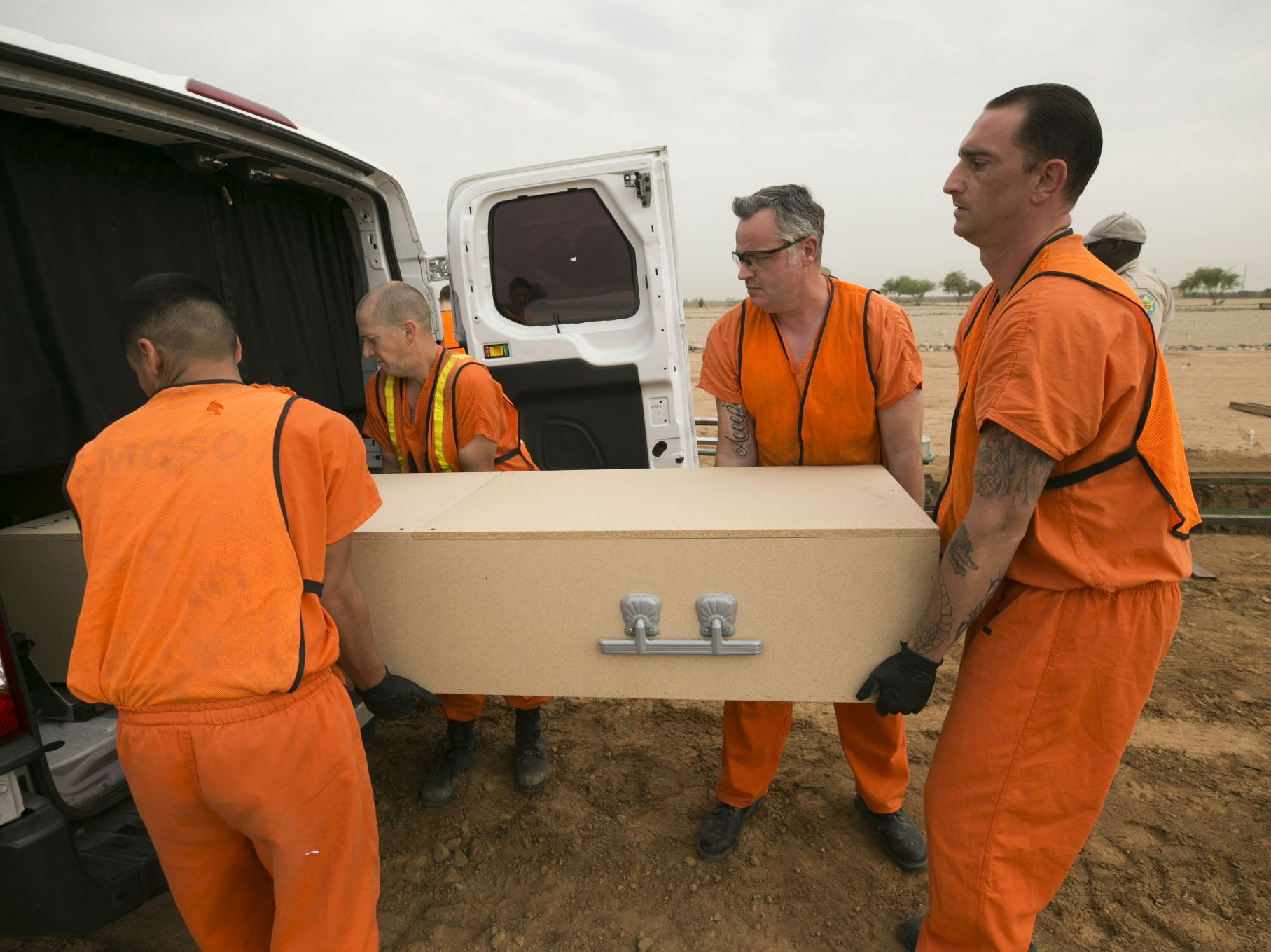 Maricopa County jail inmates assist with the burial of an indigent individual at the White Tanks Cemetery in Litchfield Park on Aug. 9, 2018.