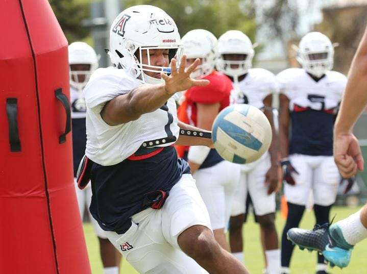 Arizona Wildcats linebacker Tony Fields II (1) lunges to block a ball during a punt-blocking drill.